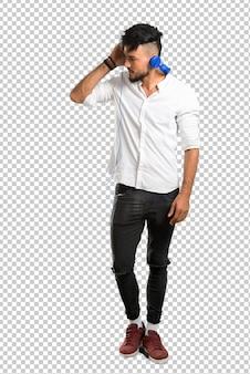 Arabische jongeman met wit overhemd luisteren naar muziek met een koptelefoon