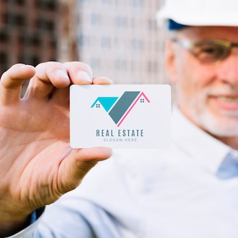 Architect die een adreskaartjemodel houdt