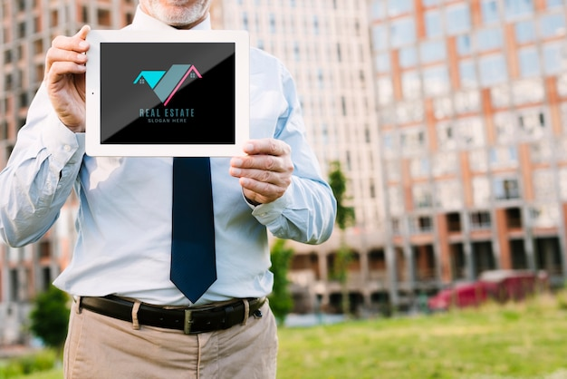 Arquitecto de vista frontal sosteniendo una maqueta de tableta
