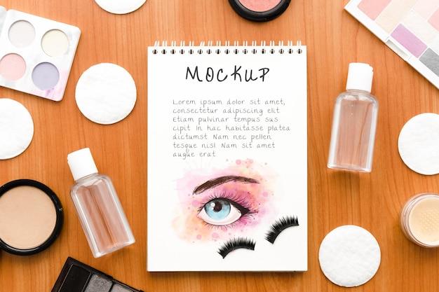 Arreglo de cosméticos de maquillaje de vista superior con maqueta de bloc de notas