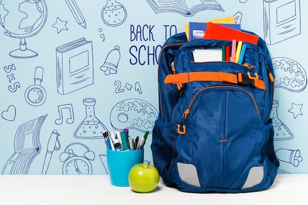 Arreglo con mochila y útiles escolares.