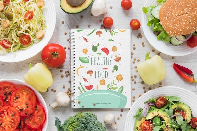 Arreglo plano con comida saludable y cuaderno
