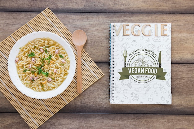 Arreglo plano con sopa y cuaderno