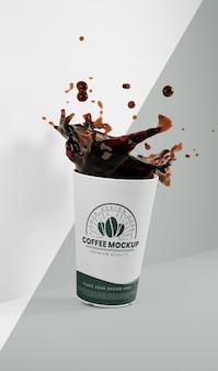 Arreglo de taza de café de papel con salpicaduras de café