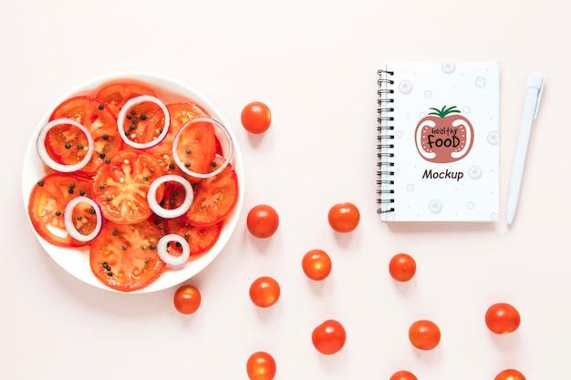 Arreglo de vista superior con tomates cherry y cuaderno