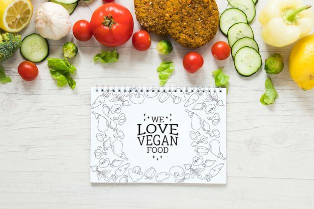Arreglo de vista superior con verduras y cuaderno