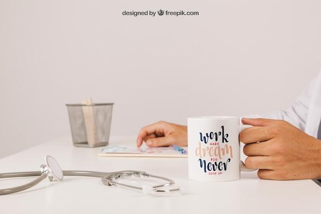 Arts aan zijn bureau met koffiemok en klembord