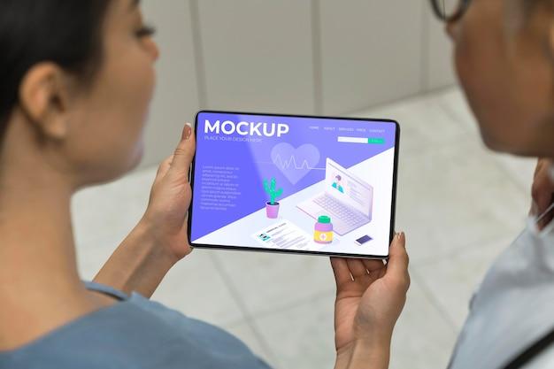 Arts en verpleegster die tabletmodel bekijken