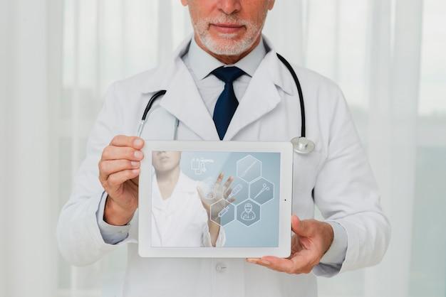 Arts met een stethoscoop die een tablet houdt