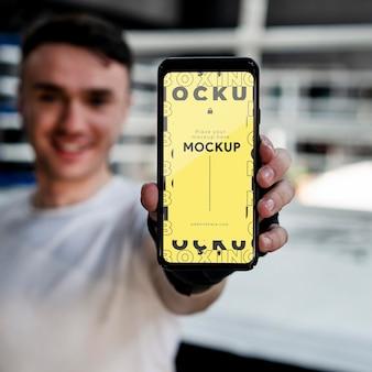 Atleta de boxeo sosteniendo un teléfono de maqueta