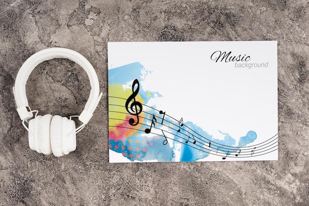 Auriculares al lado de la hoja con concepto de música
