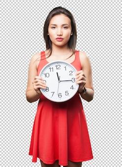 Aziatische vrouw die een klok houdt