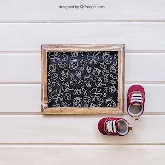 Baby mockup met leisteen en kleine schoenen