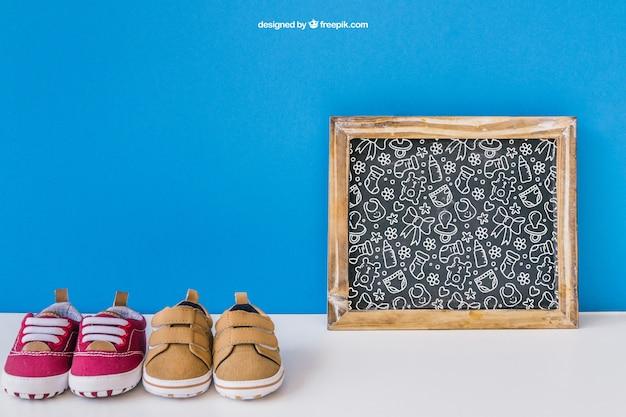 Baby mockup met leisteen en twee paar schoenen