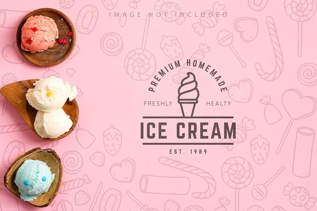 Ballen van zelfgemaakt vers koud natuurlijk kleurrijk ijs of gelato in de woooden organische schelpen op een mockup pastelroze achtergrond met kopie ruimte. bovenaanzicht.