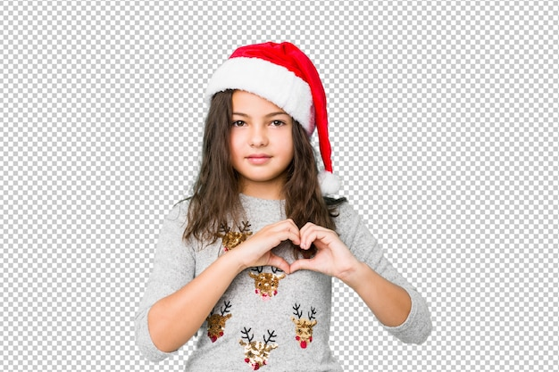 Bambina che celebra il giorno di natale che sorride e che mostra una forma del cuore con le mani.