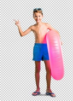 Bambino in vacanza estiva che indica il dito sul lato e che presenta un prodotto