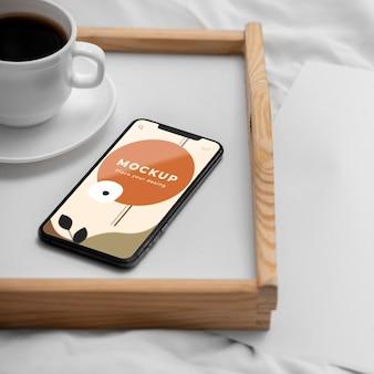 Bandeja con taza de café y móvil.