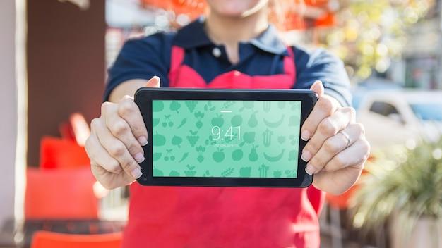 Barista sujetando mockup de tablet para presentación de app