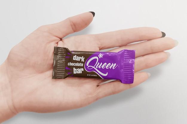 Barretta di cioccolato sul mockup di palma donna