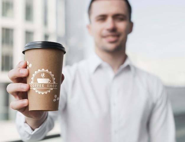 Bedrijfs mens die een model van de koffiekop steunt