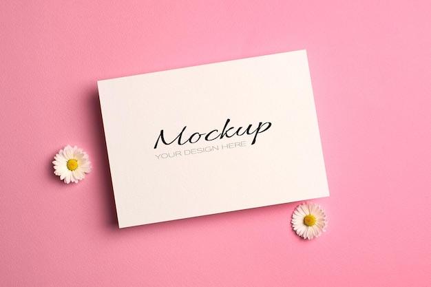 Begroetings- of huwelijksuitnodigingskaartmodel met madeliefjebloemen op roze
