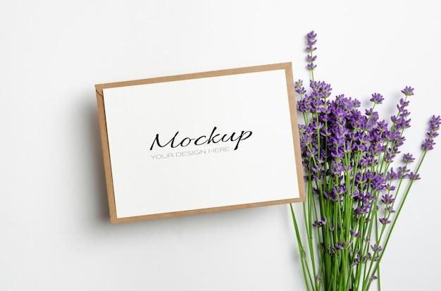 Begroetings- of uitnodigingskaartmodel met envelop en verse lavendelbloemen op wit