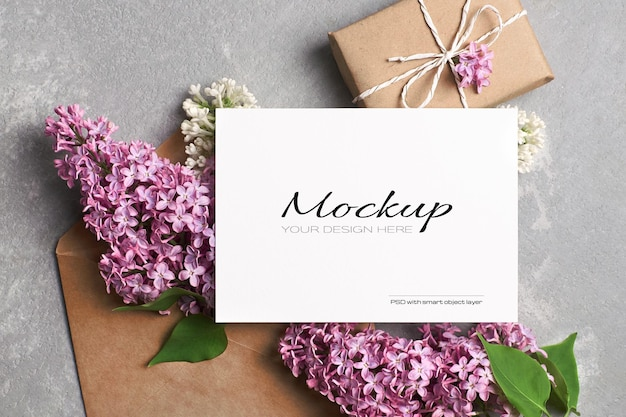 Begroetings- of uitnodigingskaartmodel met geschenkdoos, envelop en lente-lila bloemen