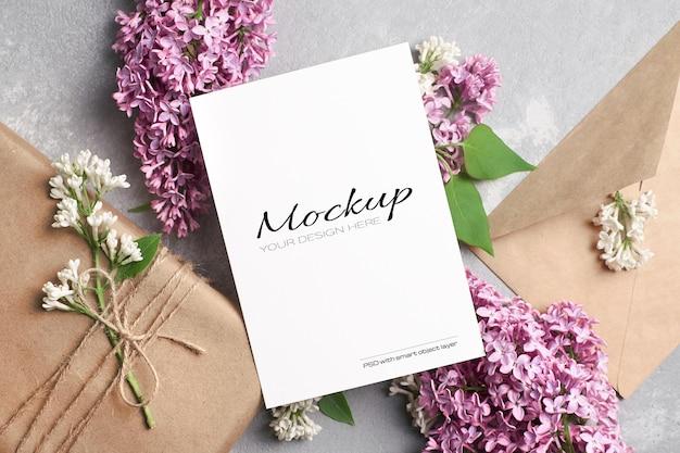 Begroetings- of uitnodigingskaartmodel met geschenkdoos, envelop en lila bloemen