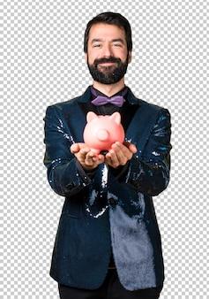 Bell'uomo con giacca di paillettes in possesso di un salvadanaio