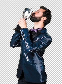 Bell'uomo con giacca di paillettes in possesso di un trofeo