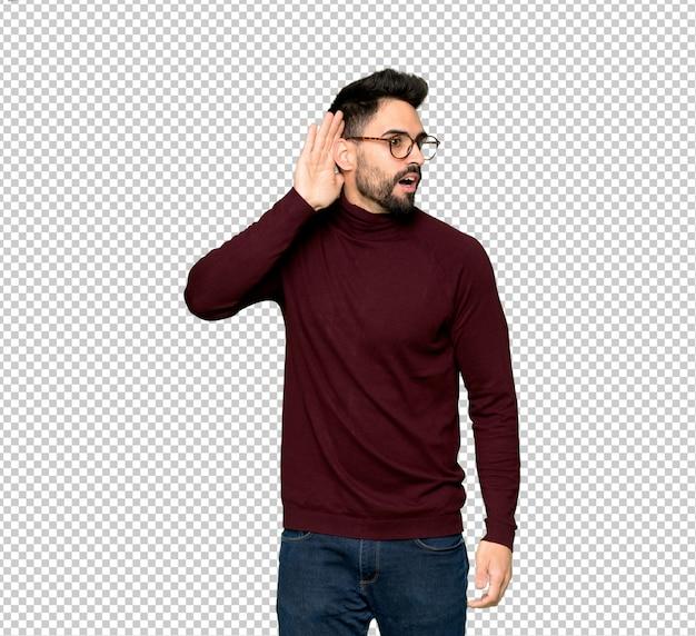 Bell'uomo con gli occhiali ascoltando qualcosa mettendo la mano sull'orecchio