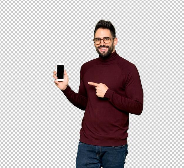 Bell'uomo con gli occhiali felice e puntando il cellulare
