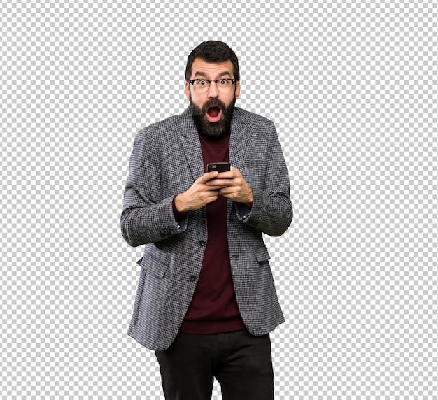 Bell'uomo con gli occhiali sorpreso e l'invio di un messaggio