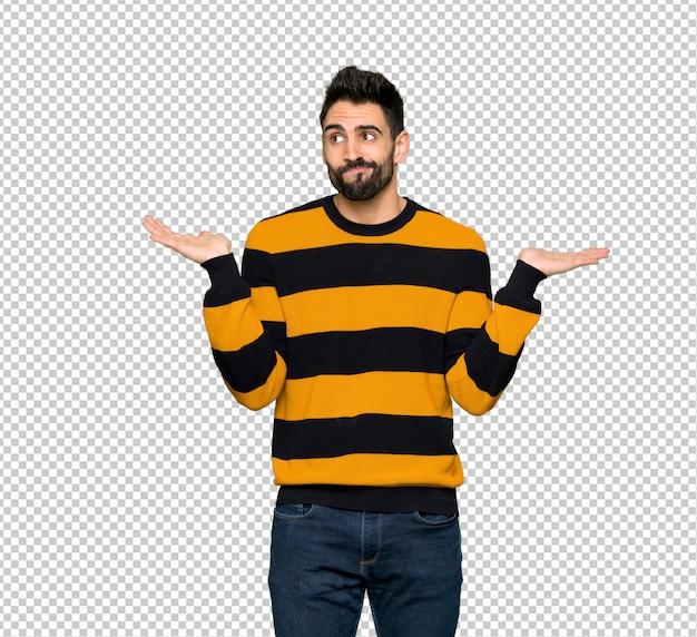 Bell'uomo con il maglione a strisce con dubbi sollevando le mani e le spalle