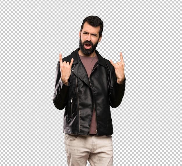 Bell'uomo con la barba che fa gesto di roccia