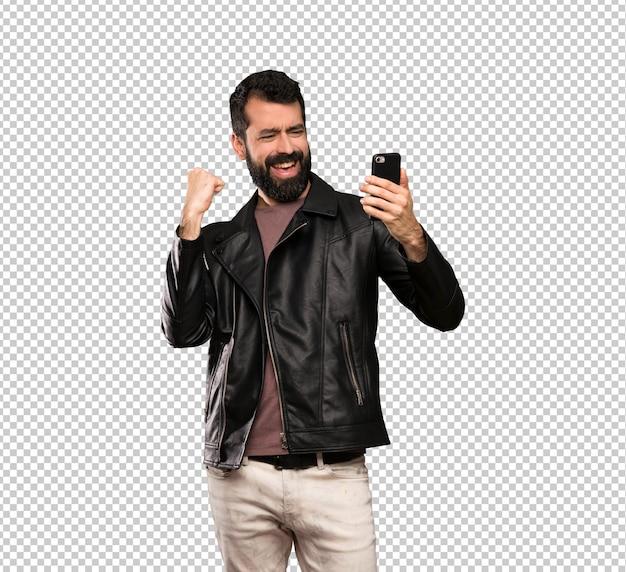 Bell'uomo con la barba con il telefono in posizione di vittoria