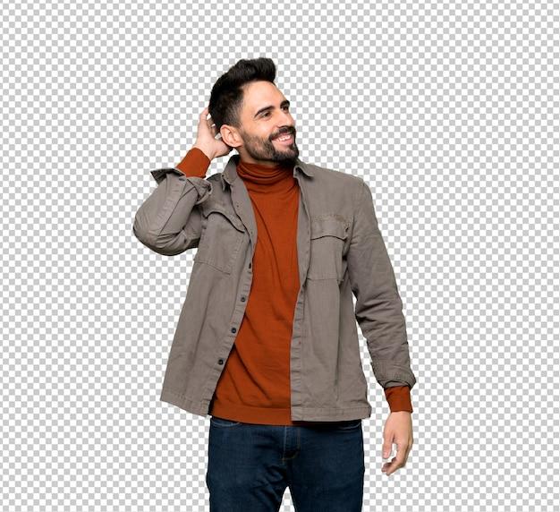 Bell'uomo con la barba pensando un'idea mentre grattando la testa