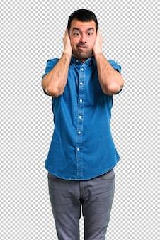 Bell'uomo con la camicia blu che copre entrambe le orecchie con le mani
