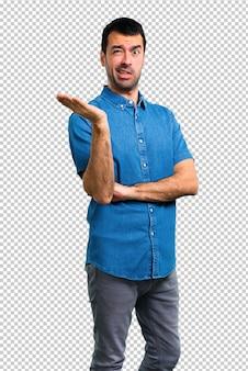 Bell'uomo con la camicia blu infelice e frustrato con qualcosa. espressione facciale negativa
