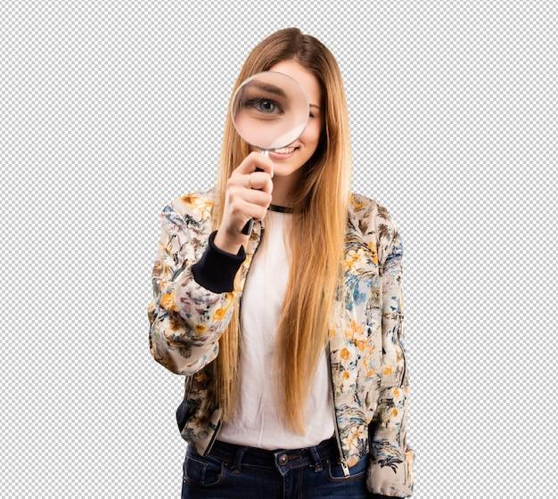 Bella giovane donna guardando attraverso una lente di ingrandimento