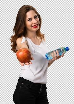 Bella ragazza con mela e acqua
