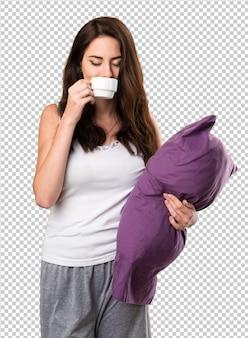 Bella ragazza con un cuscino in possesso di una tazza di caffè
