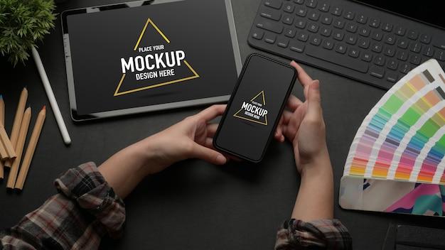 Bespeel smartphone op werktafel met mock-up tablet, toetsenbord en designer benodigdheden