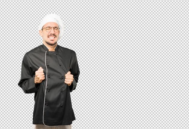 Betrokken jonge chef-kok met een spanningsgebaar