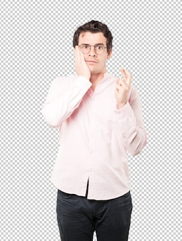 Betrokken jonge man die een gekruist vingersgebaar doet