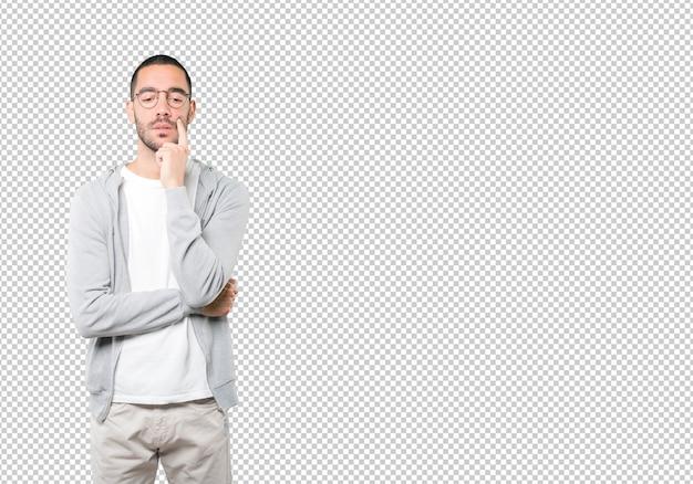 Betrokken jonge man die tegen een transparant oppervlak