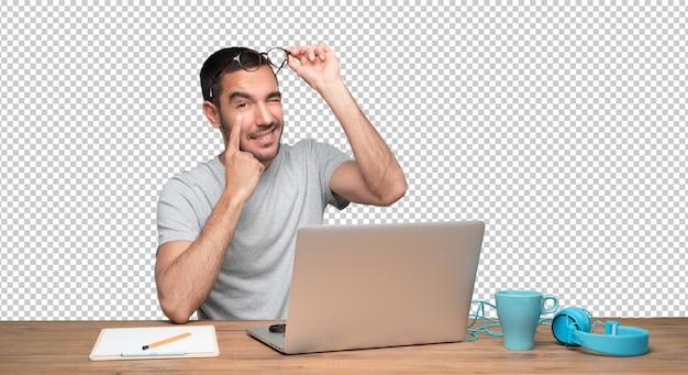 Betrokken jonge man zit aan zijn bureau en doet een gebaar van observeren