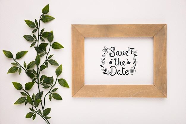 Bewaar de datum mock-up houten frame en bladeren