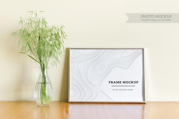 Bewerkbare psd-mockup met horizontaal a4 blanco zilveren frame met wilde bosplanten in glazen vaas